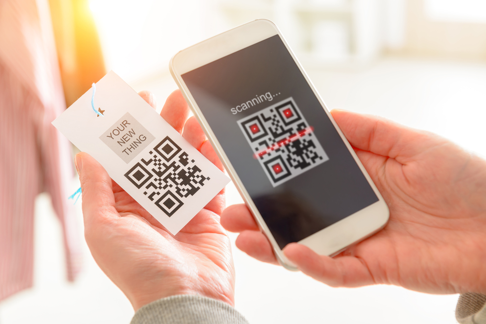 Person's hand seen holding a mobile phone and scanning QR code from a garment label in a shop