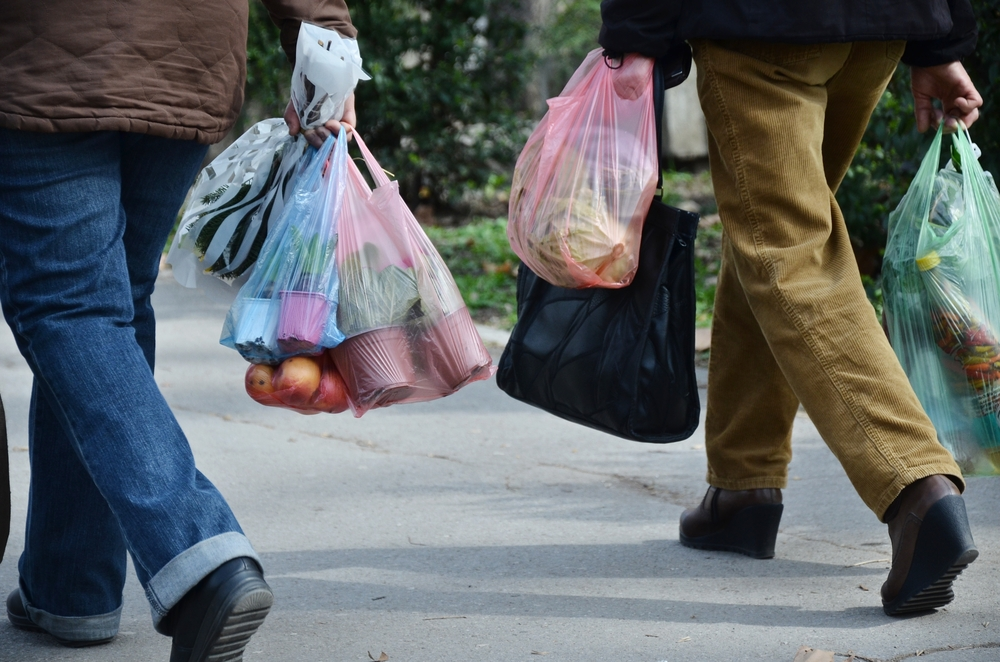 People's feet are shown walk and they have plastic shopping bags in their hands.