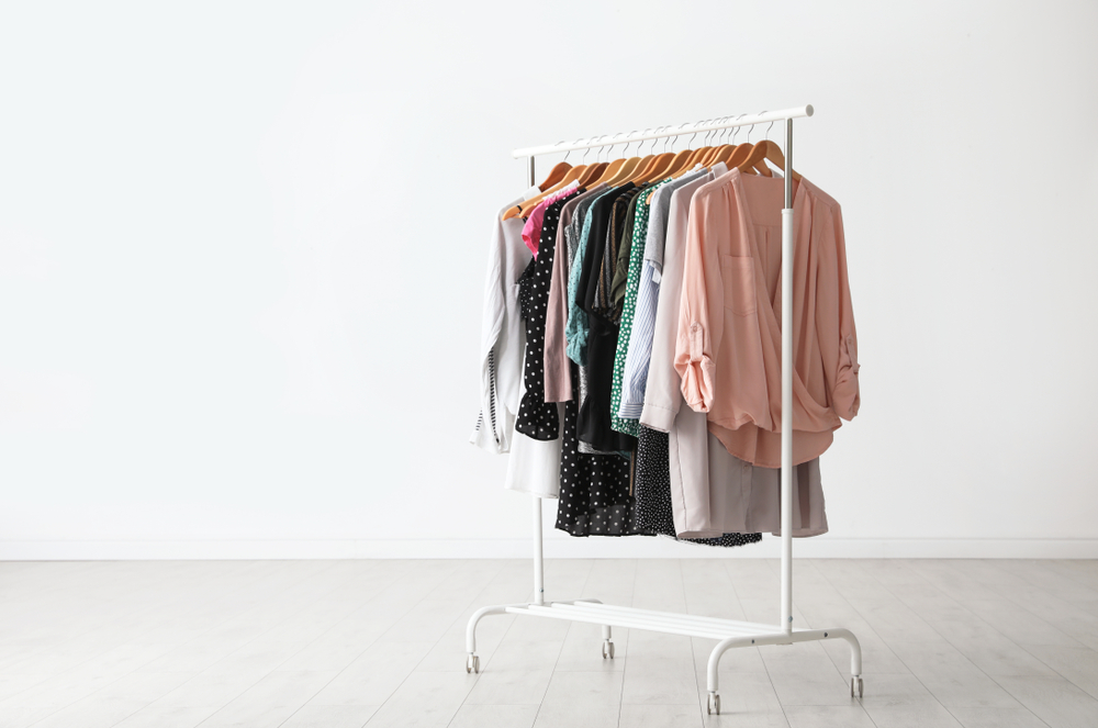 Wardrobe rack with clothes hanging near white wall indoors