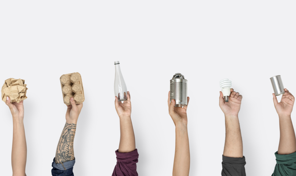 People's hands in the air, each hold different types of packaging, paper, carton, glass bottle, aluminum cans