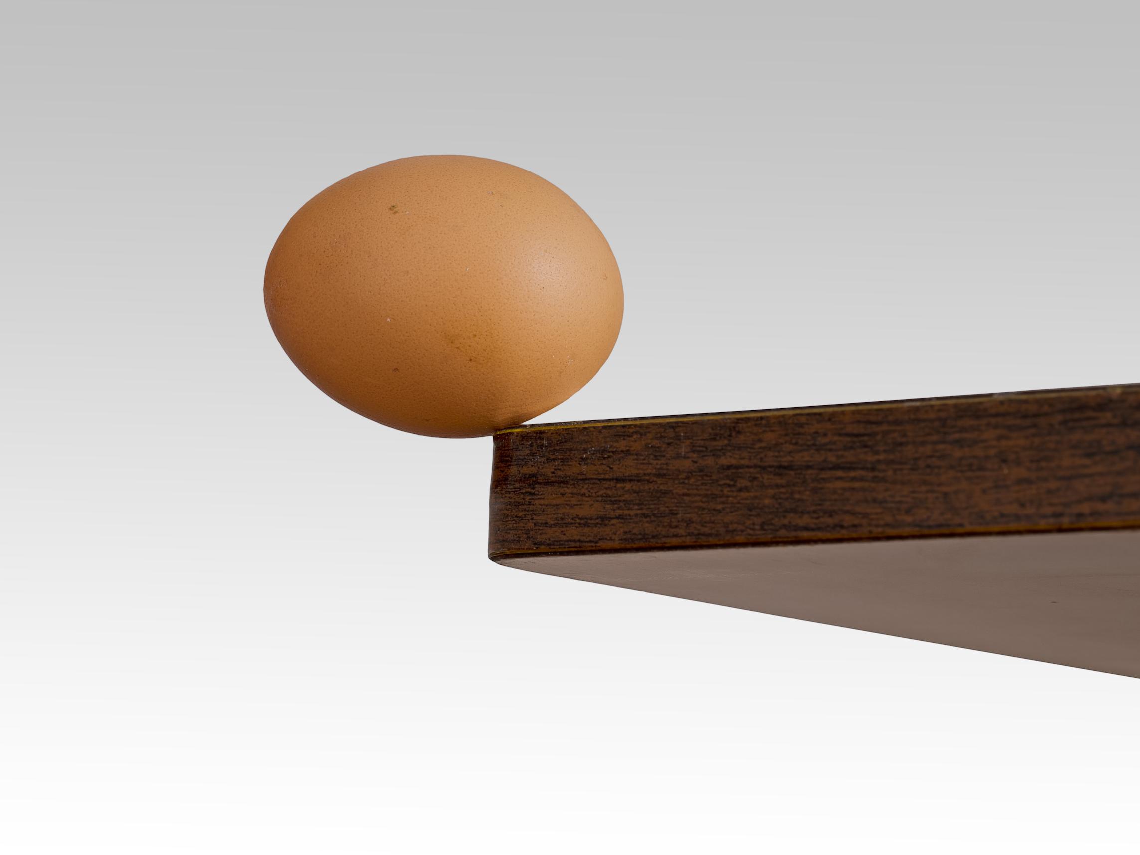 Egg balanced on edge of table