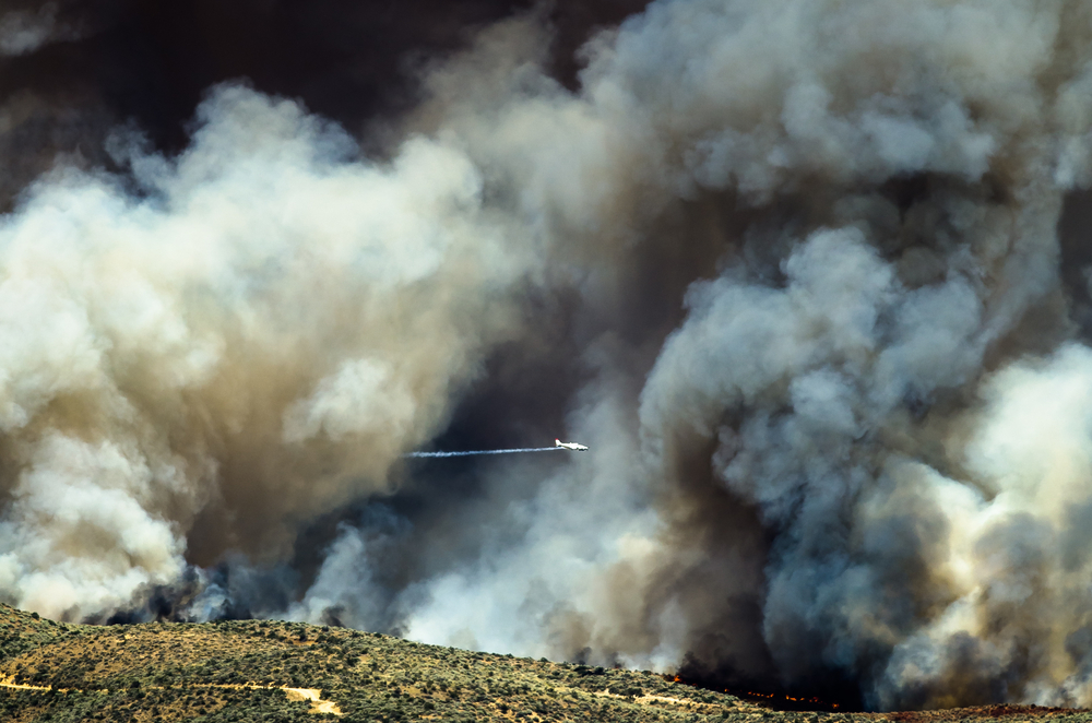 Aircraft flying through the dense white smoke rising from a raging wildfire