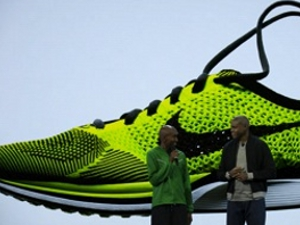 U.S. Olympic team members Carl Lewis and Abdi Abdirahman discuss Nike's Flyknit shoe.