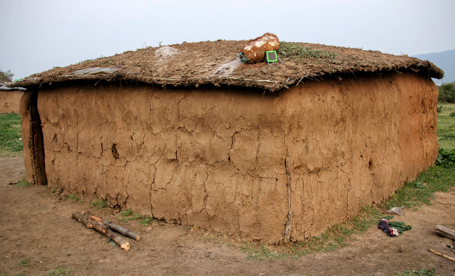 A solar cell-phone charger on the roof of a Masai village home, next to a decoy of a calf used to keep cows lactating
