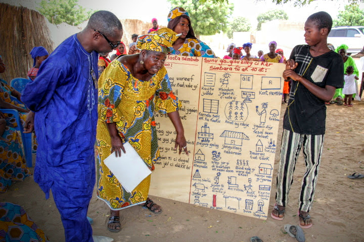 Senegalese villagers display the community action plan for health, sustainability and commerce