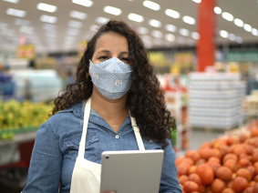 Worker in a grocery store, wearing a mask