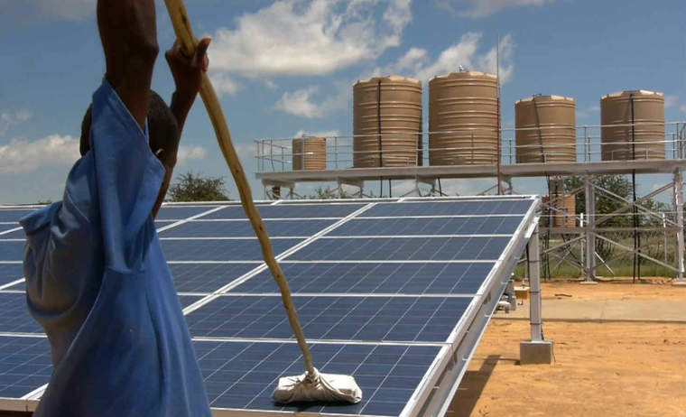 Worker cleans solar panels at a desalination plant in Akutsima, Namibia