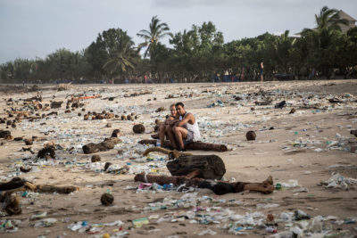Vacationers in plastic-covered Kuta Beach
