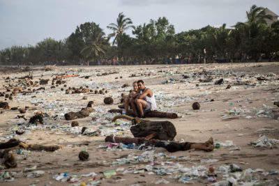 Vacationers in plastic-covered Kuta Beach