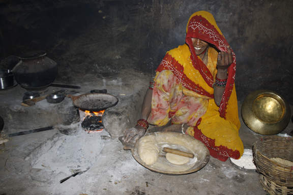 Woman cooking roti and dal over traditional cookstove