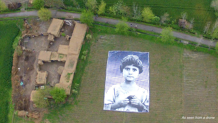 An aerial view of the site that includes the photo of a child killed by a drone attack.