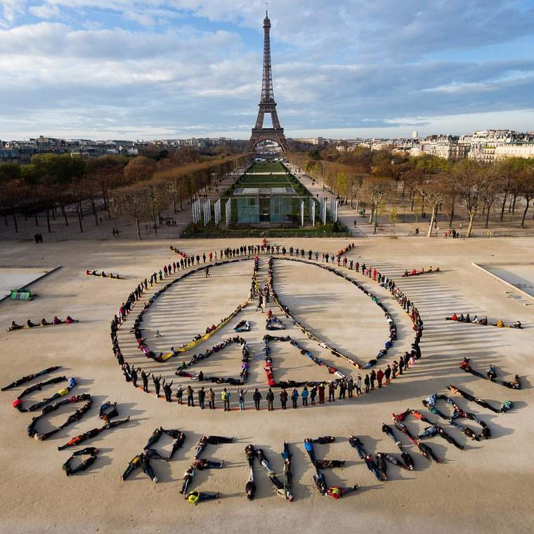 Hundreds of activists lie down to connect peace with the Paris climate talks at the base of the Eiffel Tower.