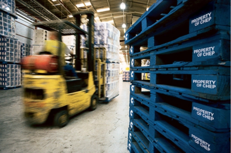 forklift lifting pallets in warehouse