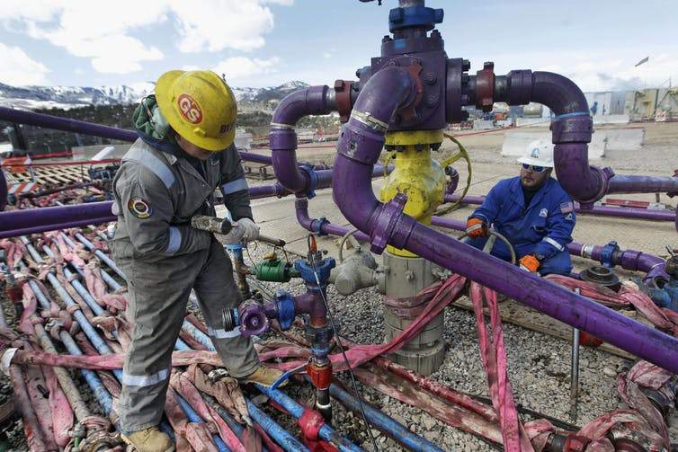 Workers tend to a well head during a hydraulic fracturing operation