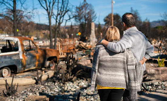 Couple observes debris after fire disaster