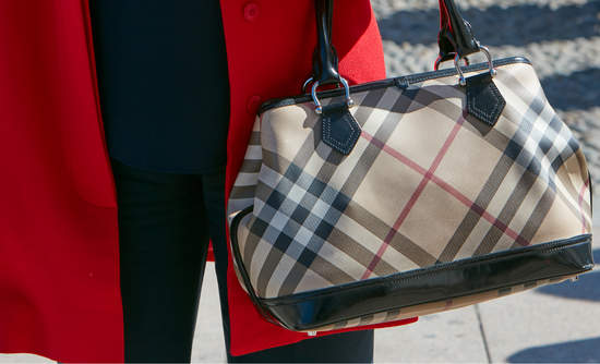A woman clutching a Burberry purse at Milan Fashion Week in 2017.