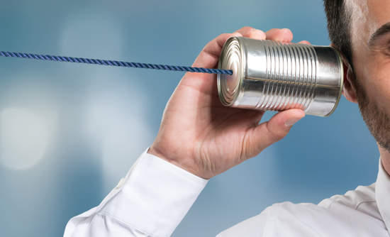 Businessman holding a tin phone can to his ear