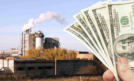 Fan of hundred-dollar bills next to a smokestack