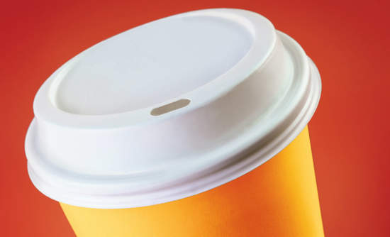 Disposable coffee cup looms ominously against red background