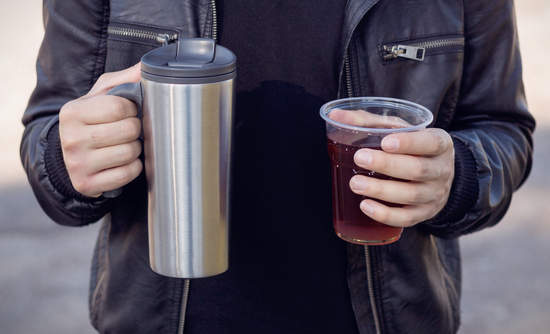person holding reusable coffee cup and plastic coffee cup