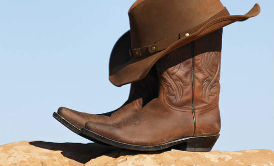 Cowboy hat and boots on dry soil