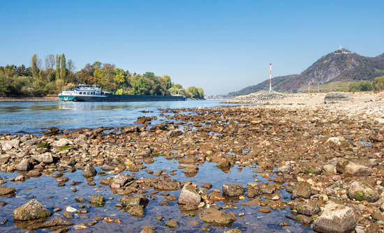 Inland navigation vessel with reduced shipload on dried out Rhine River with low water level, caused by prolonged drought 2018