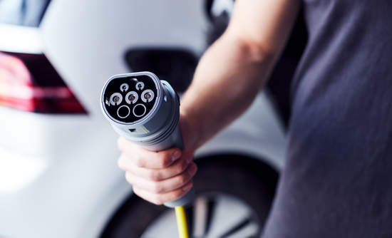 Close up of person holding power cable for zero-emissions electric car.