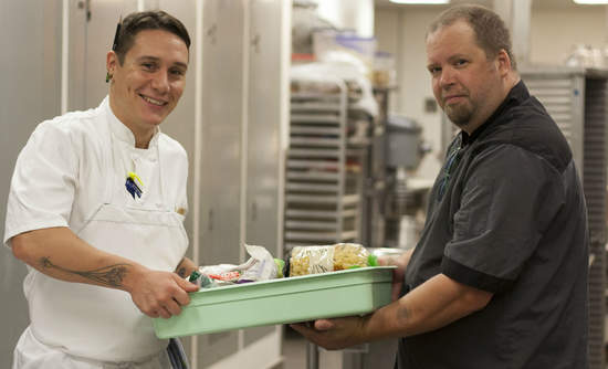 Taylor Johnson from Bon Appétit's TASTE Restaurant at the Seattle Art Museum hands off recovered food to Mike from Operation Sack Lunch, a Food Lifeline partner.