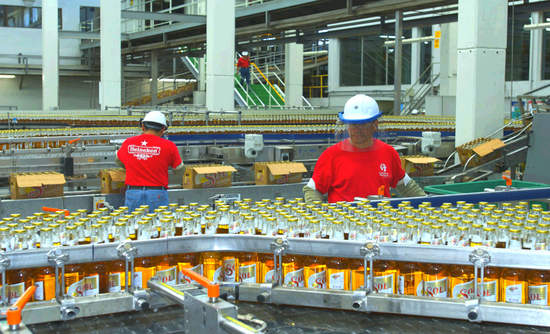 Heineken plans to set science-based emission-reduction targets and buy more renewable energy. Above, workers oversee a bottling line at a Heineken brewery in Mexico.