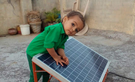 Boy in green shirt in rural India leans on solar panel
