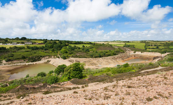 Abandoned mine and tailings dam at Wheal Maid Valley in Cornwall, England.