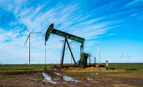 Oil rig pumping oil in West Texas with huge wind farm creating renewable energy in background.