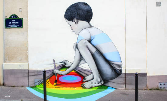 Graffiti in Paris of a child painting a rainbow