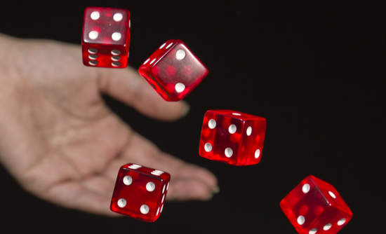 A female hand rolling several red dice.