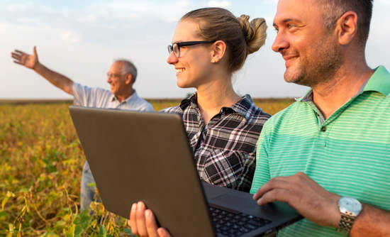 Group of farmers with laptop standing in a field examining soybean crop