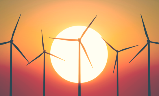 wind turbines in front of a sun