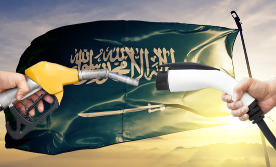 hands holding electric charging and gas pump in front of Saudi flag
