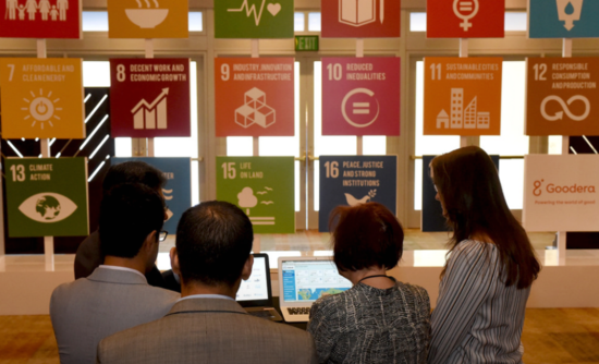 People look at the Goodera app in front of a display of the U.N. Global Goals in the hallway of the GreenBiz 18 conference in Phoenix.