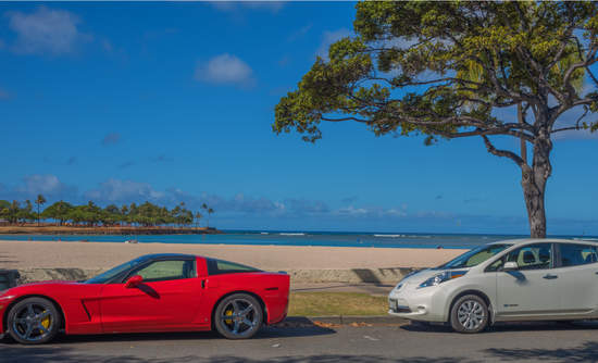 Past and future? A red sports car and an EV drove up to a beach...