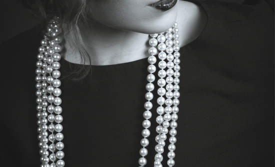 A woman in a Coco Chanel-inspired little black dress with pearls