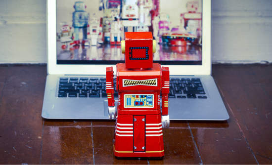 Red toy robot looking at an open laptop