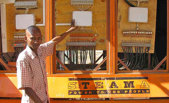 SteamaCo agent John Pambio stands beside the controls at the solar-panel hub in Entasopia, which is located in the village chief's yard.