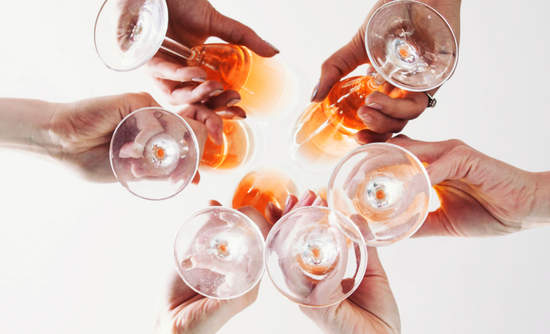 Image of hands toasting wine glasses