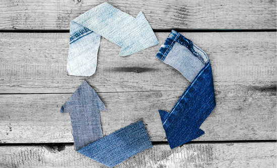 Denim scraps in the shape of the three-arrows recycling symbol