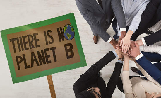 a climate protest sign next to corporate handshave