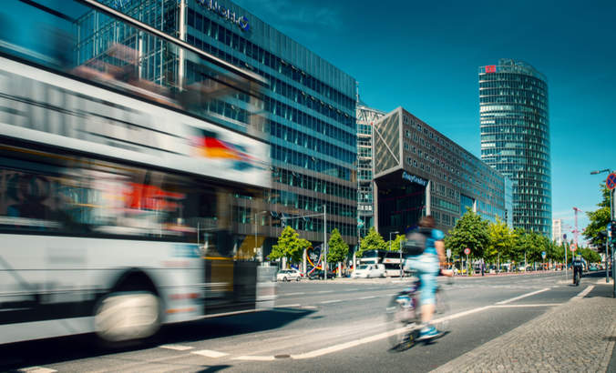 Cyclist riding alongside a bus at Potsdamer Platz in Berlin, Germany.