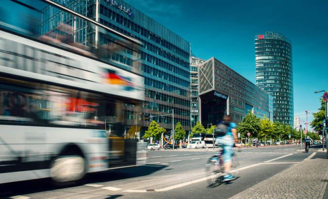 Cyclist riding alongside a bus at Potsdamer Platz in Berlin, Germany.