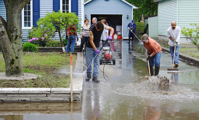 Volunteers cleanup outside of a suburban home following catastrophic flooding in Quebec, Canada