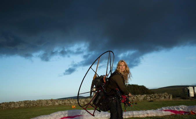 """Sacha Dench, dubbed the """"Human Swan,"""" wearing a paramotor on her back."""