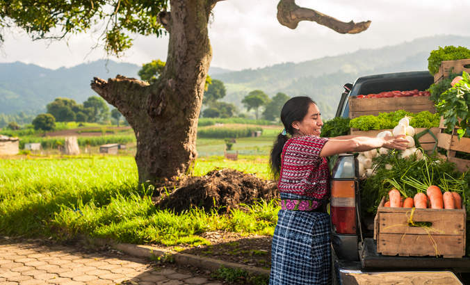Indigenous woman with her truck full of vegetables in a rural area of Guatemala